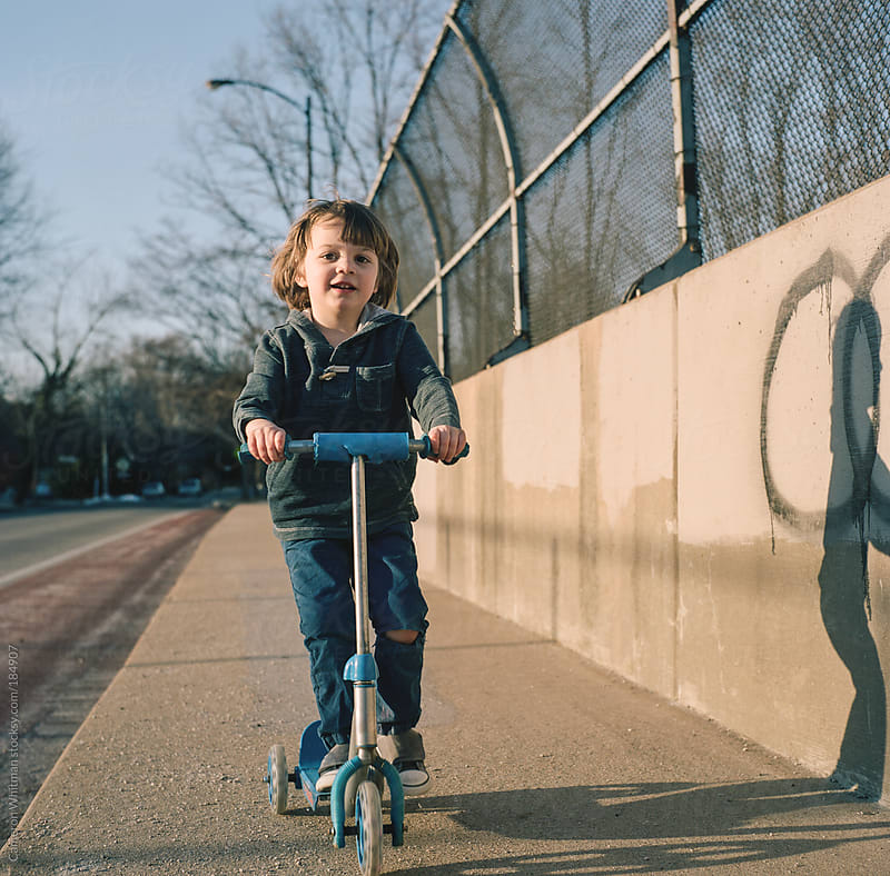 Boy riding a scooter by Cameron Whitman for Stocksy United