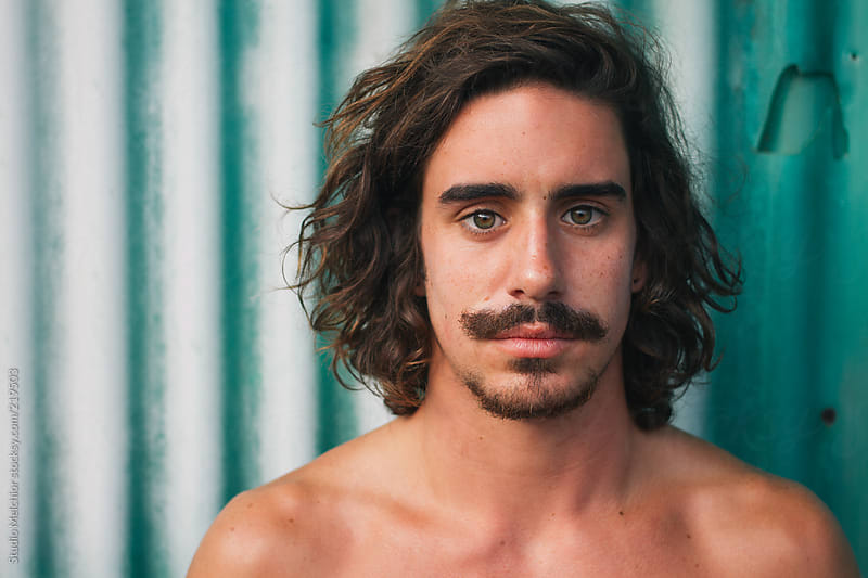 Surfer with moustache at a green background by MELCHIOR / PHOTOGRAPHER for Stocksy United
