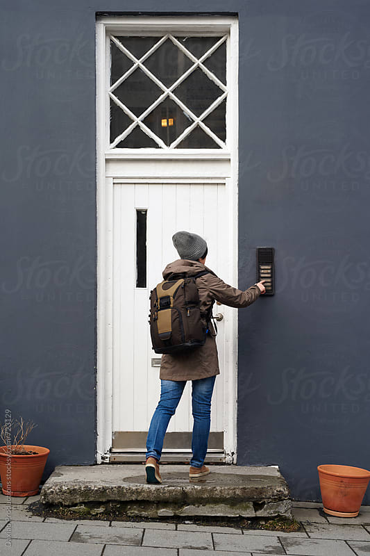 Woman ringing entrance door  by Daxiao Productions for Stocksy United
