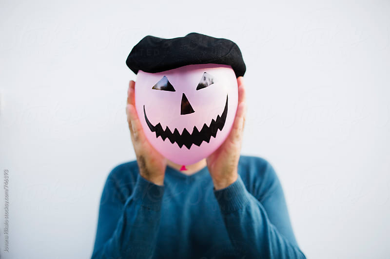 Man  holding halloween balloon in front of his face by Jovana Rikalo for Stocksy United