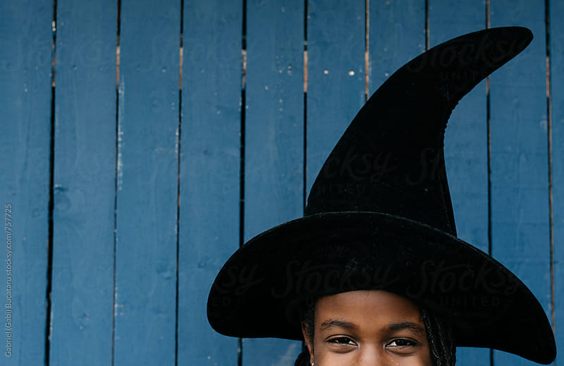 Black girl wearing a witch hat for Halloween by Gabriel (Gabi) Bucataru for Stocksy United