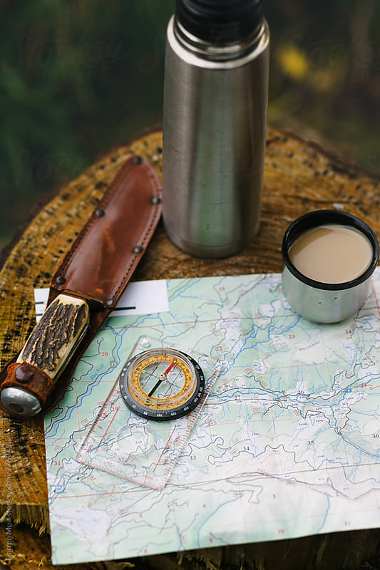 Plotting a trail on a map, while having a coffee break. by Darren Muir for Stocksy United