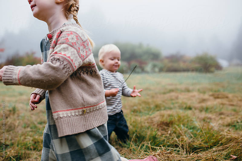Little Girl jauntily walking past her baby brother on a field on a foggy day by Amanda Voelker for Stocksy United