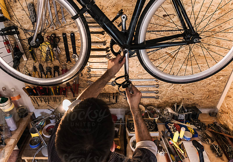 Young mechanic working on bike maintenance in his rustic workshop. by Audrey Shtecinjo for Stocksy United