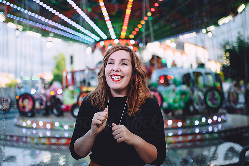portrait in front of a carrousel by Thais Ramos Varela for Stocksy United
