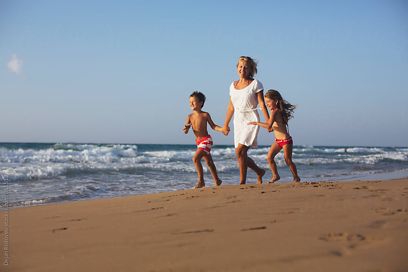 Family taking a walk on the beach. by Dejan Ristovski for Stocksy United