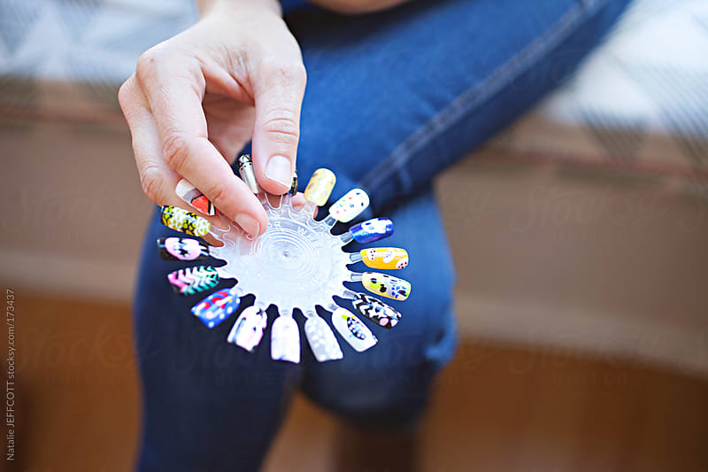 A lady waiting to get a manicure and choosing nail art design from sample wheel by Natalie JEFFCOTT for Stocksy United