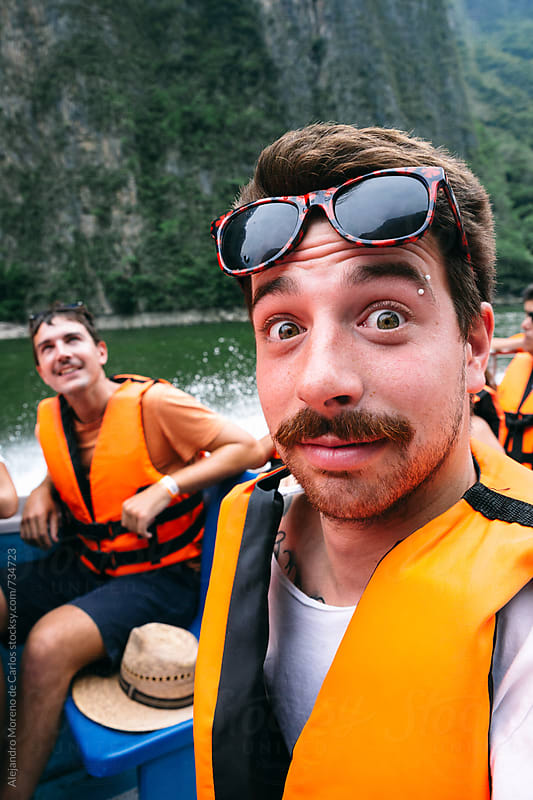 Young man pulling funny face while traveling on a boat with his friends by Alejandro Moreno de Carlos for Stocksy United