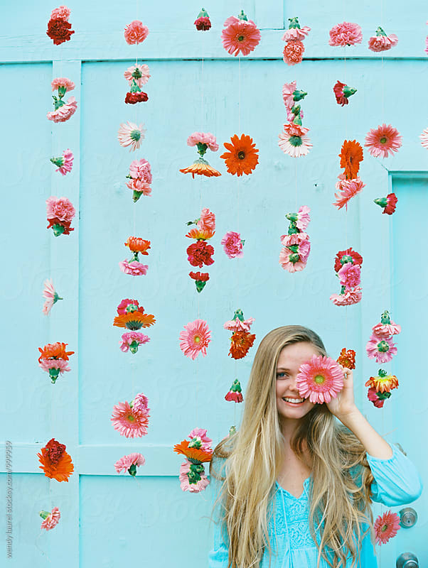 pink flower over eye on blonde girl with hanging pink flowers