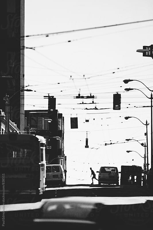 Silhouette of man rollerblading through busy urban street, Seattle, WA, USA by Paul Edmondson for Stocksy United