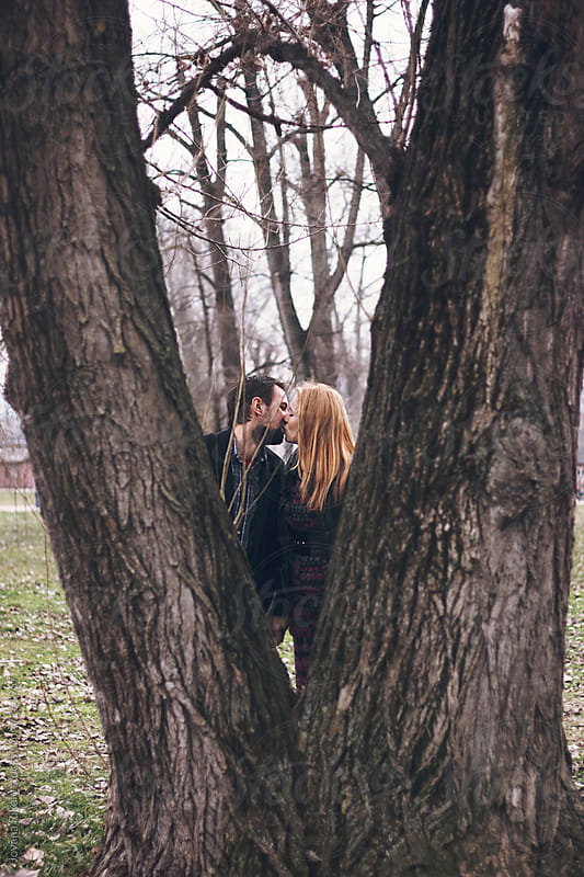 Couple kissing each other behind the double tree by Jovana Rikalo for Stocksy United