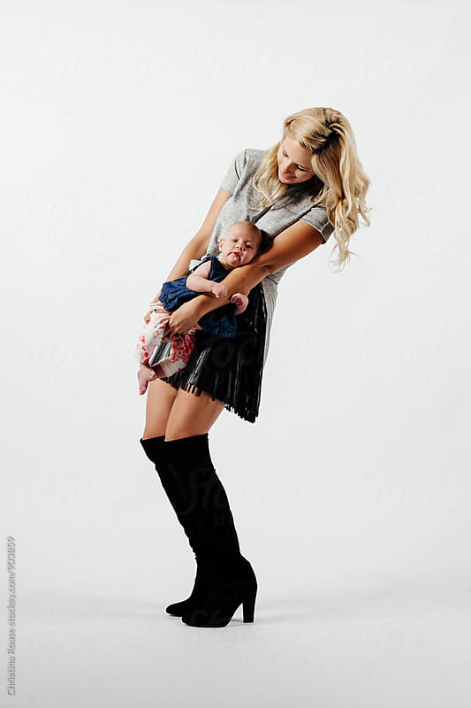 Fashionable mother holding baby girl in a studio setting by Christina Rouse for Stocksy United
