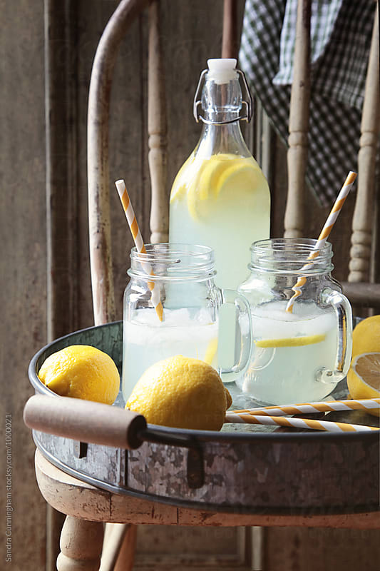 Homemade lemonade with jam jar glasses and straws by Sandra Cunningham for Stocksy United