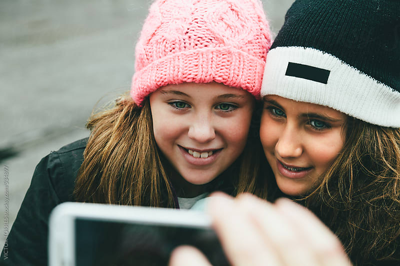 Two Little Girls Taking a Selfie by VICTOR TORRES for Stocksy United