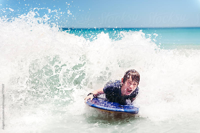 Boy having fun on a boogie board at the beach by Angela Lumsden for Stocksy United