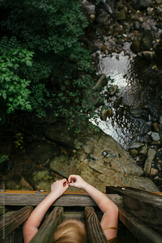 Birds Eye View of Girl On a Bridge over a stream by Amanda Voelker for Stocksy United
