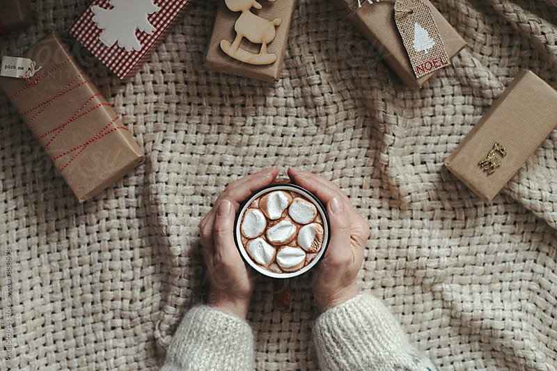 Drinking cocoa surrounded by Christmas gifts by Pixel Stories for Stocksy United
