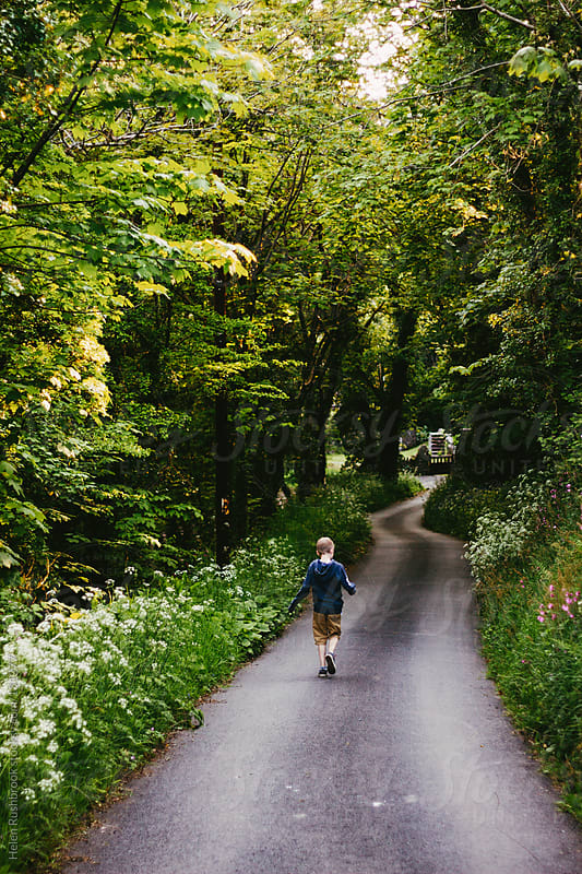 A young boy walking down a wildflower-lined country road by Helen Rushbrook for Stocksy United