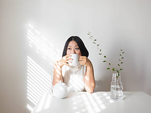 26e42a8ea67 Portrait of young woman sipping tea at table with natural light