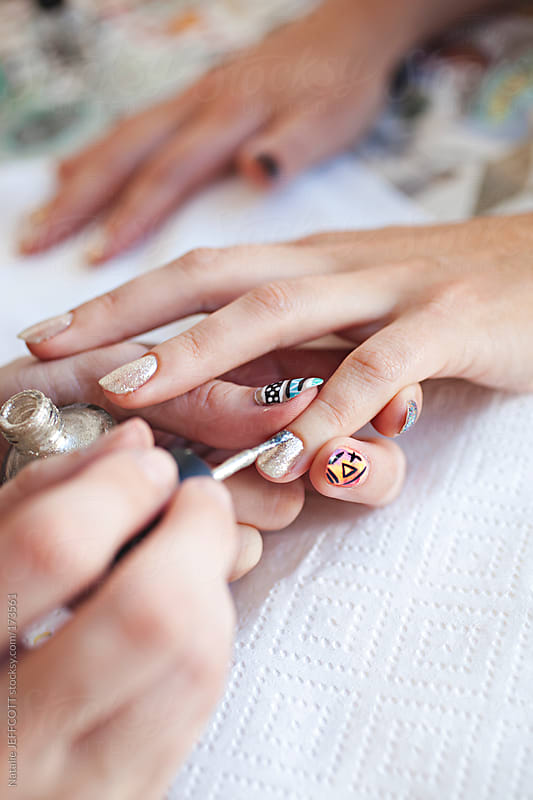 close up of manicurist painting a lady's fingernails with silver polish by Natalie JEFFCOTT for Stocksy United