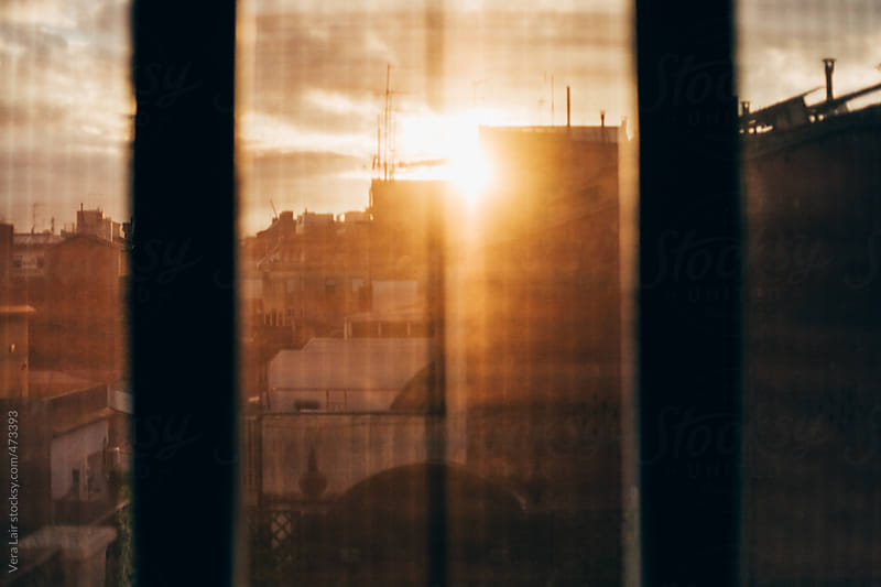 View of sunset behind a window by Vera Lair for Stocksy United
