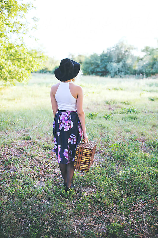 Back view of a young woman in floral dress holding a picnic basket by Jovana Rikalo for Stocksy United