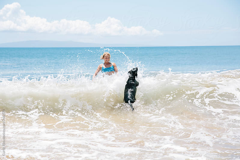 Blonde female jumping over waves with her dog by Curtis Kim for Stocksy United