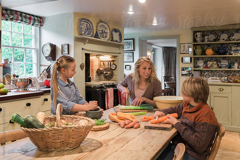 Mother and two children prepairing a meal in an old country style kitchen. by Paul Phillips for Stocksy United