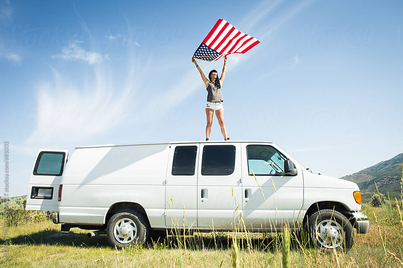 Woman Holding American Flag on Van Roof by MEGHAN PINSONNEAULT for Stocksy United