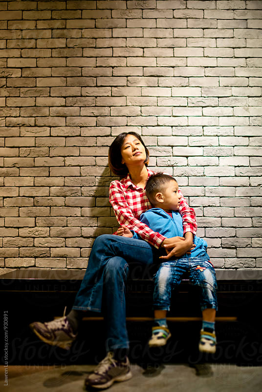 Woman hugging her son while sitting on bench  by Lawren Lu for Stocksy United