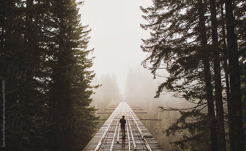 man standing on that PNW bridge on a foggy day by Sam Hurd Photography for Stocksy United