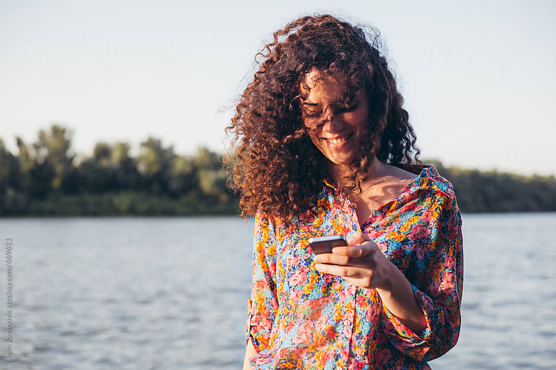 Cute girl with curly hair texting on her phone by the river by Jovo Jovanovic for Stocksy United
