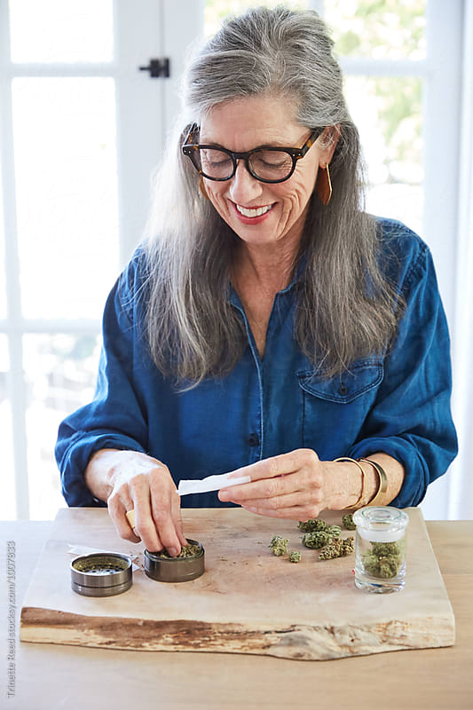 Senior woman using medical marijuana/cannabis by Trinette Reed for Stocksy United