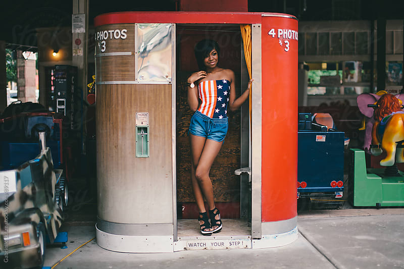 Black girl in Americana top standing in a Photo Booth  by Gabrielle Lutze for Stocksy United