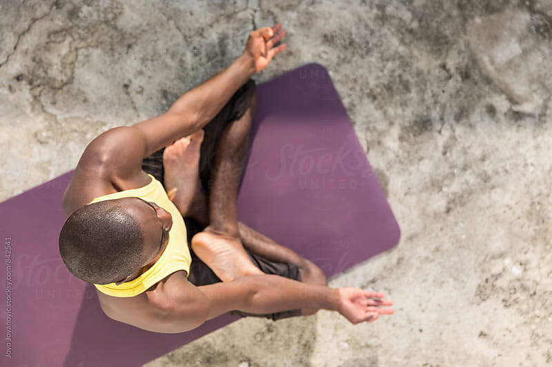 Aerial shot of a man sitting in a meditation yoga pose by Jovo Jovanovic for Stocksy United