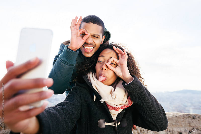 Couple taking a funny selfie above city on winter. by BONNINSTUDIO for Stocksy United