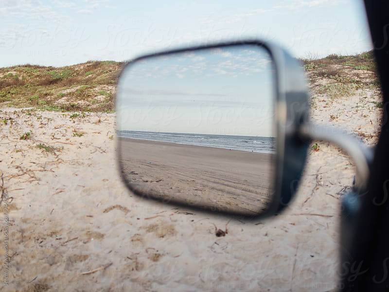 Ocean in mirror of car parked on beach by Jeremy Pawlowski for Stocksy United