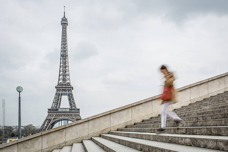 A woman walking down the stairs with the Eiffel Tower in the background by michela ravasio for Stocksy United
