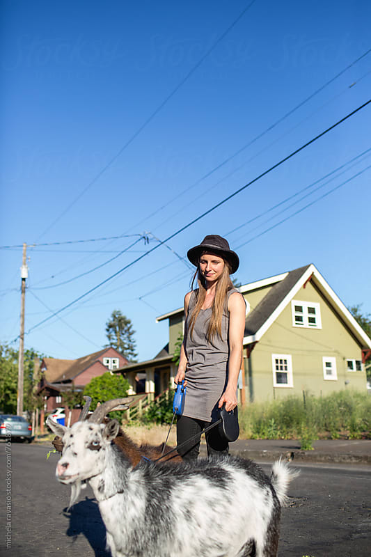 Woman walks with her goats in the neighborhood by michela ravasio for Stocksy United