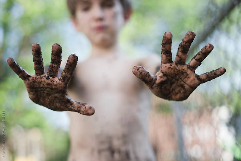 Boy holds out his muddy hands by Cara Dolan for Stocksy United