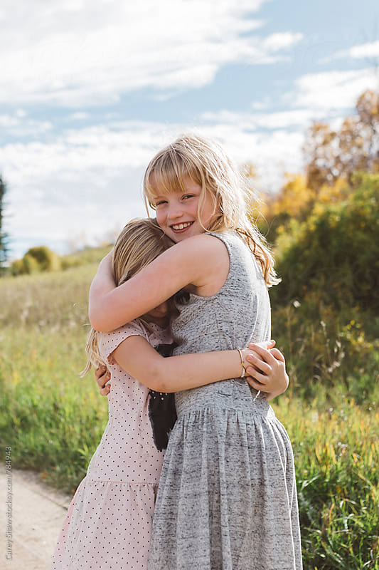 Young girl hugging shy sister by Carey Shaw for Stocksy United