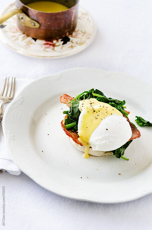 Eggs benedict florentine with hollandaise sauce, spinach and bacon by Jill Chen for Stocksy United