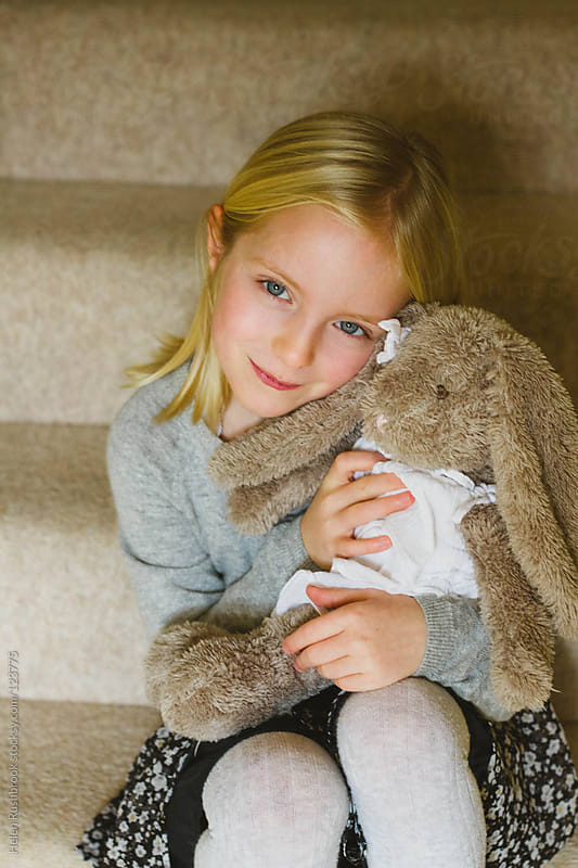 Sweet portrait of a little girl with her toy rabbit by Helen Rushbrook for Stocksy United