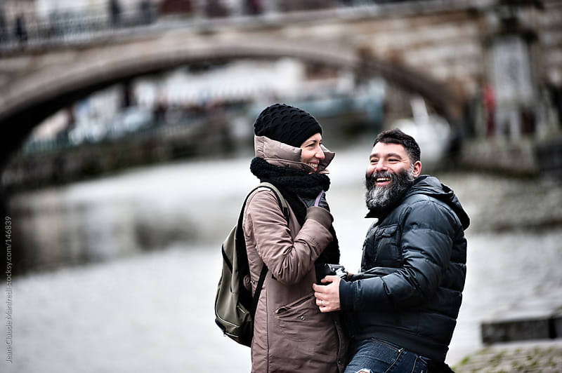 Young loving couple laughing on a walk along a canal by Jean-Claude Manfredi for Stocksy United