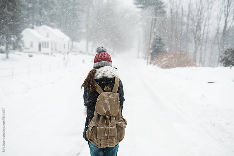 woman walking down a snowy road with backpack  by Léa Jones for Stocksy United