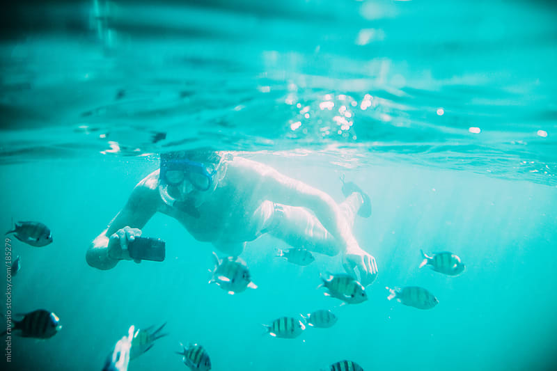 Man snorkeling and taking a picture underwater by michela ravasio for Stocksy United