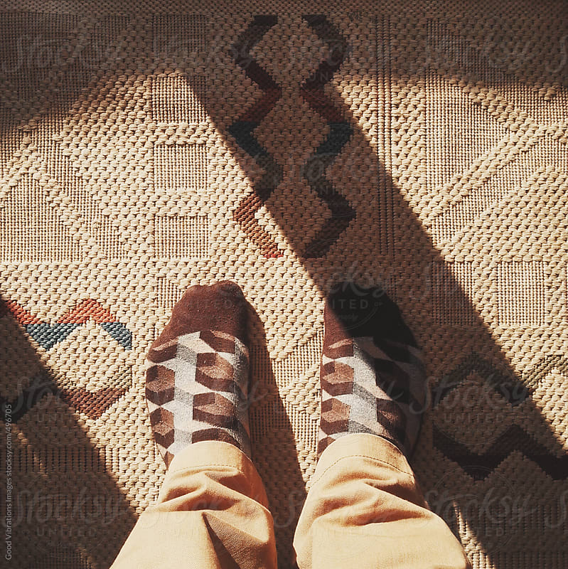 Man standing with vintage socks on a vintage carpet by Good Vibrations Images for Stocksy United