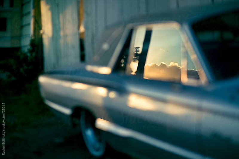 Sunset clouds reflected in the window of a vintage car by Rachel Bellinsky for Stocksy United