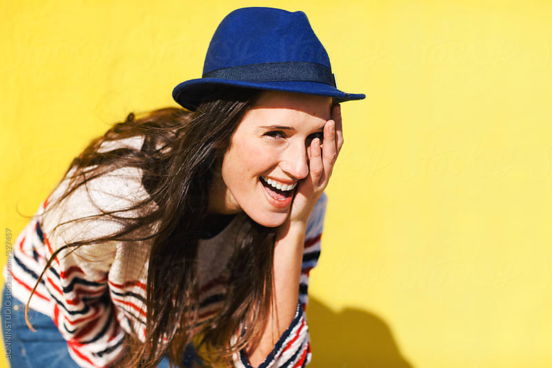 Young casual woman smiling in front of a yellow wall. by BONNINSTUDIO for Stocksy United