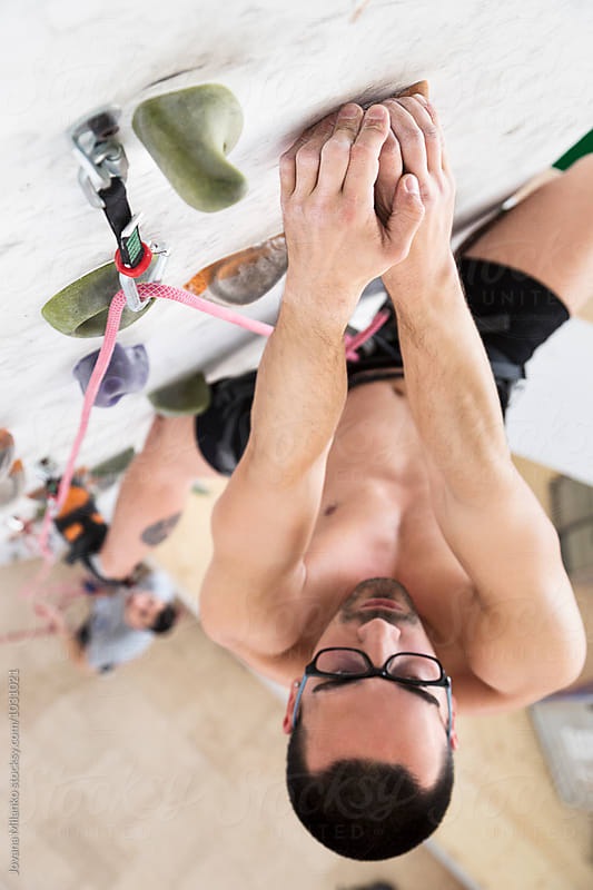 Rock climber exercising on an indoor climbing wall  by Jovana Milanko for Stocksy United